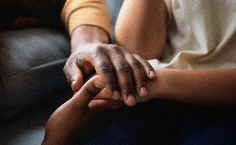 Image: A Black man holds the hand of a child