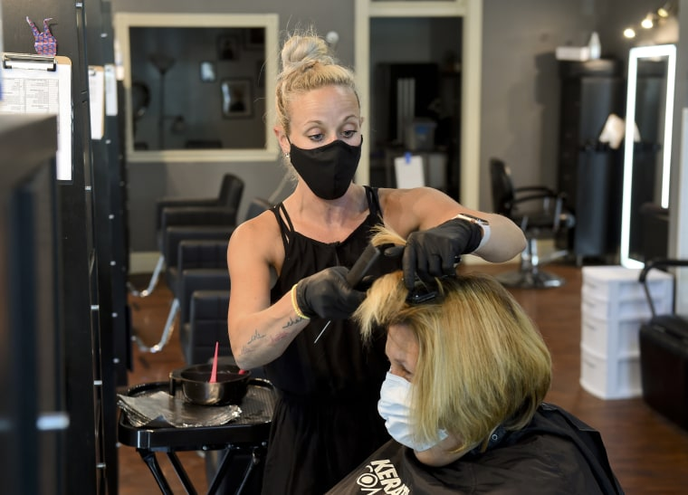 Stephanie DeLozier, owner of Salon Avanti, cuts a customer's hair while they both wear masks in West Reading, Pa., on 26, 2020.