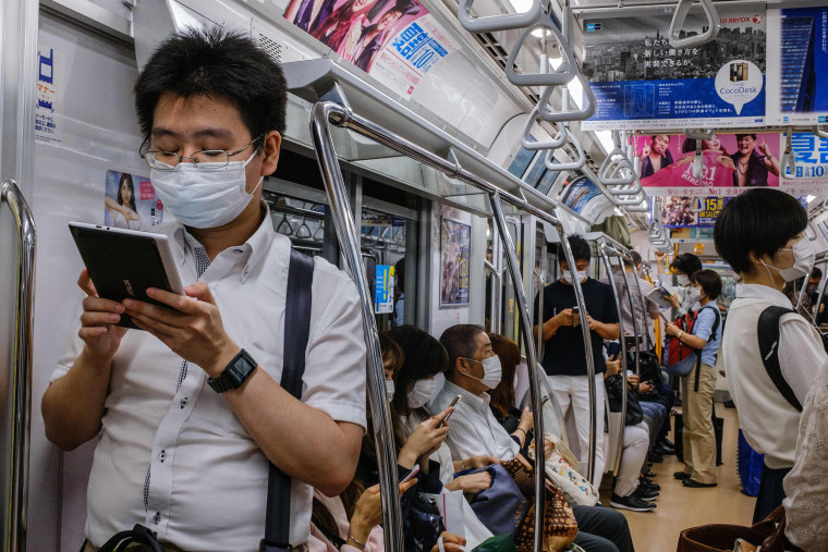 Image: Commuters wearing face masks travel on a train in Tokyo on July 16, 2020.