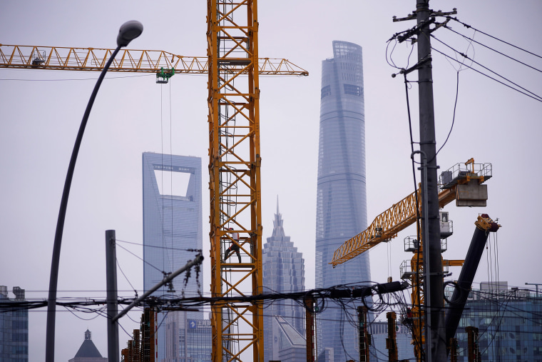 Image: A worker is seen on a crane at a construction site in front of Lujiazui financial district, in Shanghai