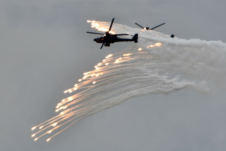 Image: Two US-made AH-64E Apache attack helicopters release flares during the annual Han Kuang military drills in Taichung