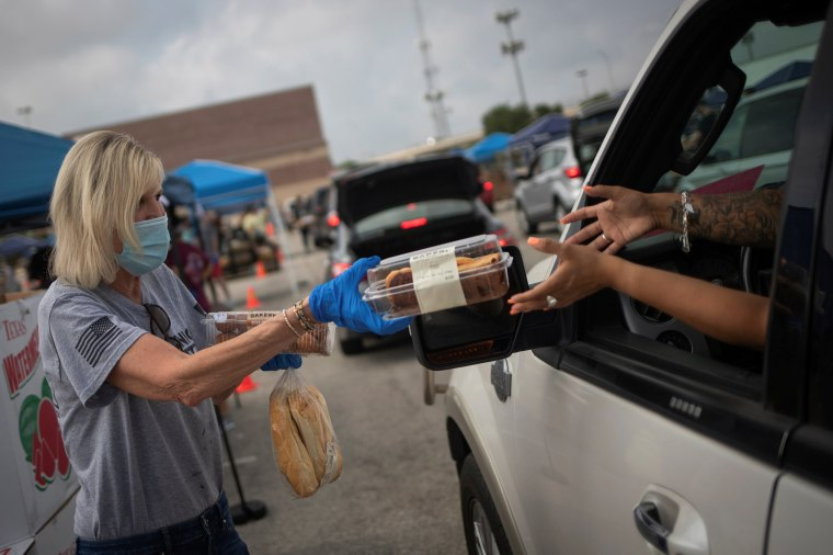 Image: Volunteer give food to residents economically affected by COVID 19 pandemic during San Antonio Food Bank distribution in Texas