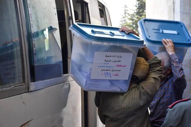 Image: Syrian men carry ballot boxes