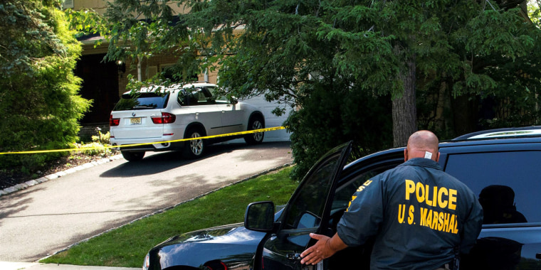 Law enforcement officials are seen outside the home of federal judge Esther Salas, where her son was shot and killed and her defense attorney husband was critically injured, in North Brunswick, N.J., on July 20, 2020.