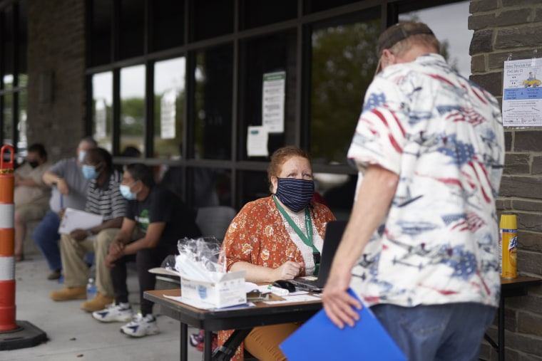 One-stop operator Vickie Gregorio with the Heartland Workforce Solutions talks to a jobseeker outside the workforce office in Omaha, Neb., on July 15, 2020.