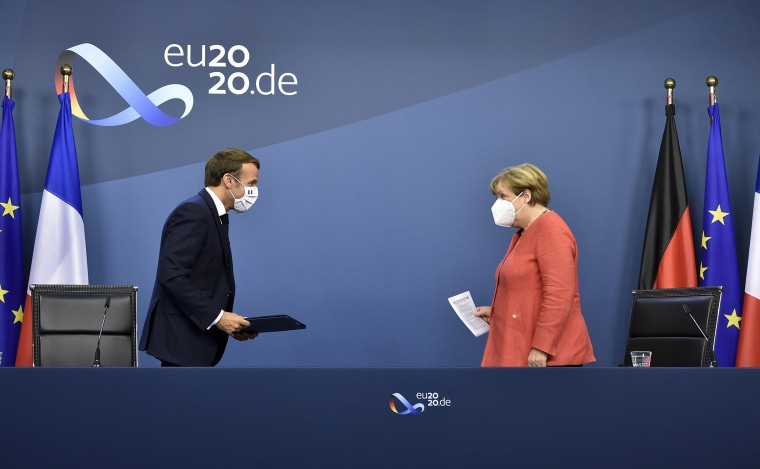 Image: German Chancellor Angela Merkel, right, and French President Emmanuel Macron prepare to address a media conference at the end of an EU summit