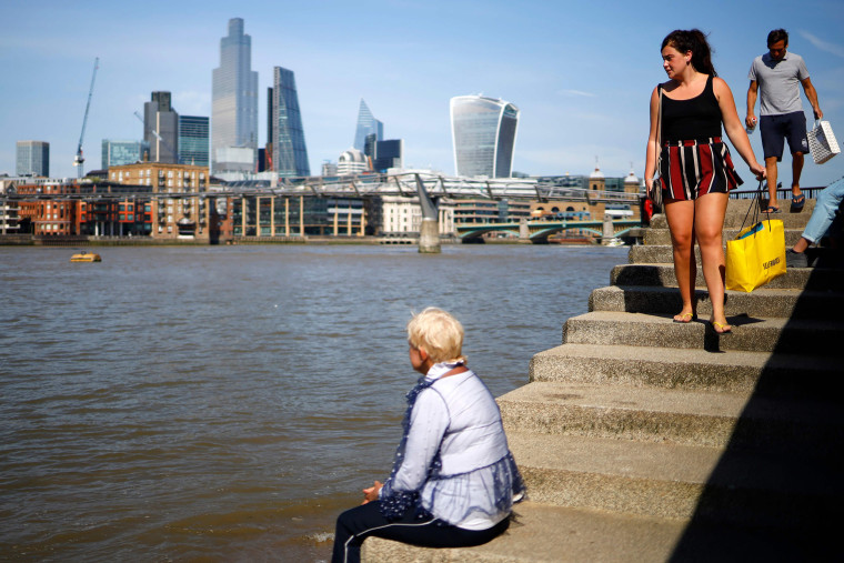 Image: A woman holding a Selfridges bag walks down steps beside the River Thames in the sunshine in London