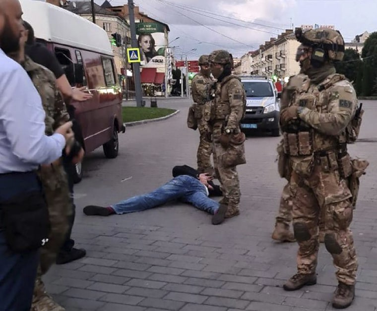 Image: An assailant, who seized a long-distance bus with 10 hostages, lies on the ground after police officers captured him in the city centre of Lutsk,