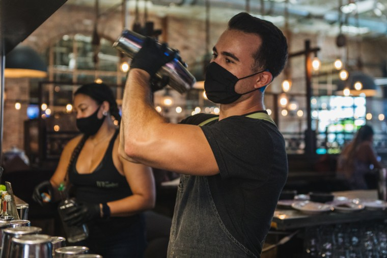 Employees wearing protective masks and gloves prepare drinks at a restaurant in Fort Lauderdale, Fla., on June 25, 2020.