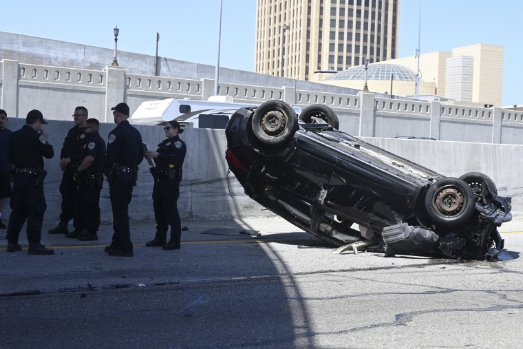 California Highway Patrol officers stand by an overturned car at an accident site on the Interstate 101 freeway in downtown Los Angeles on June 14, 2020.