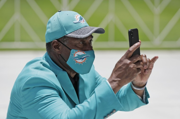Former Miami Dolphins player Nat Moore wears a mask while taking a photo of guests at a tribute procession for coach Don Shula in Miami Gardens, Fla., on May 22, 2020 .