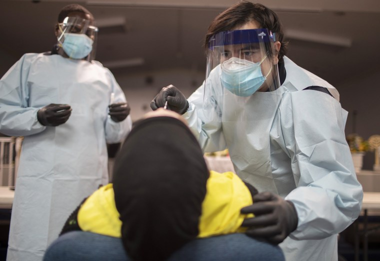 Health care workers use a nasal swab to test a person for COVID-19 at a pop up testing site in Pembroke Park, Fla., on July 22, 2020.