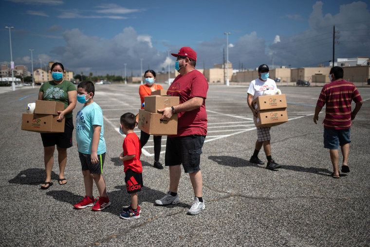 Image: Residents affected by economic fallout from the pandemic hold groceries provided by the Houston Food Bank in Texas