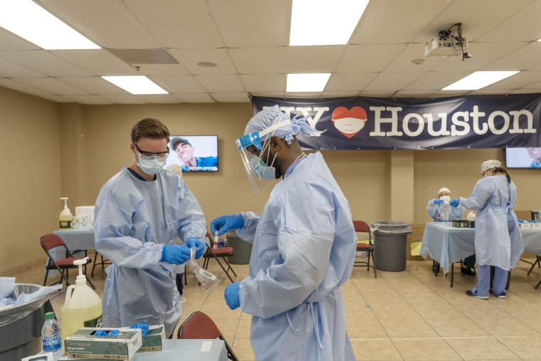 Medical workers from New York handle test samples at a coronavirus test site in Houston on July 17, 2020.