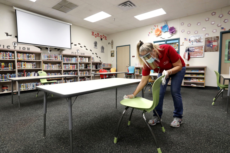 Wearing a mask and face guard as protection against the spread of COVID-19, Garland Independent School District custodian Maria Concha wipes down a chair in the library at Stephens Elementary School in Rowlett, Texas, on July 22, 2020.