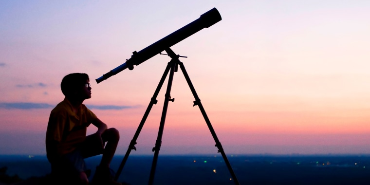 Person stargazing at night with a telescope. Shop the best telescopes and binoculars to watch meteor showers.