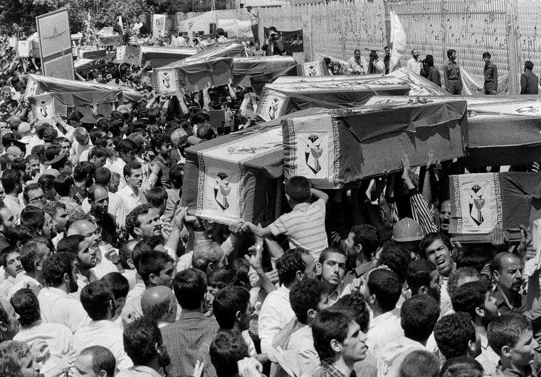 Mourners carry coffins through the streets of Tehran, Iran, during a mass funeral for the victims aboard Iran Air flight 655, which was shot down by the USS Vincennes in the Persian Gulf, on July 7, 1988.