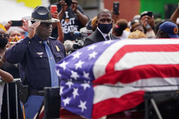 An Alabama State Trooper salutes the casket carrying the late Rep. John Lewis, a pioneer of the civil rights movement who died July 17, after it was carried across the Edmund Pettus Bridge in a horse-drawn carriage in Selma, Ala., on July 26, 2020.
