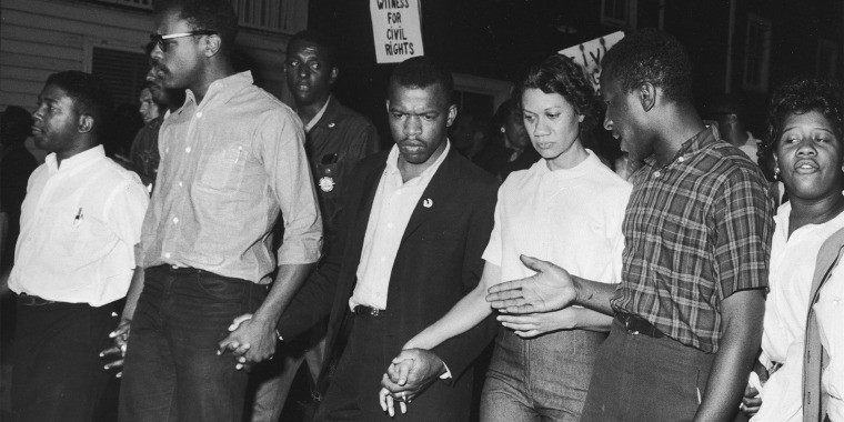 Civil rights leaders, including John Lewis, third from left, and Gloria Richardson, third from right, links hands with others as they march in protest of a scheduled speech by the pro-segregationist governor of Alabama, George Wallace, in Cambridge, Md., in May 1964.