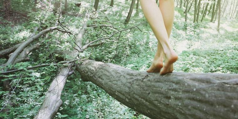 Woman walking on log in beech forest