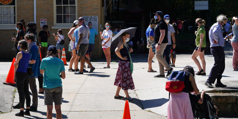 People stand in line to get tested for COVID-19 at a free walk-up testing site in Atlanta on July 11, 2020.