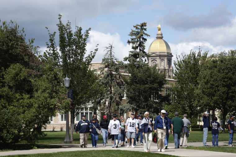 Image: Fans walk near the Main Building on the University of Notre Dame campus in South Bend, Indiana, on Sept. 8, 2012.