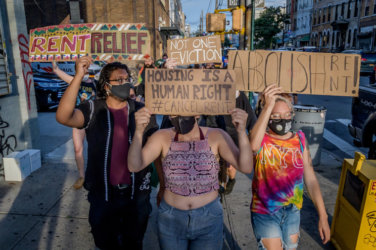 Protesters hold signs as they march against evictions in Brooklyn, New York, on July 5, 2020.