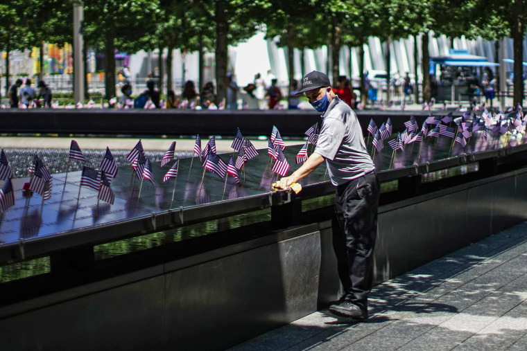 A worker disinfects the area of one of the reflecting pools as people visit the 9/11 Memorial Plaza on July 4, 2020, in New York.