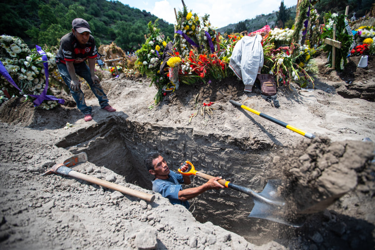 Gravediggers work digging several graves at the same time due to high demand during the pandemic at the San Miguel Xico cementery in Valle de Chalco, Mexico, on July 13, 2020.