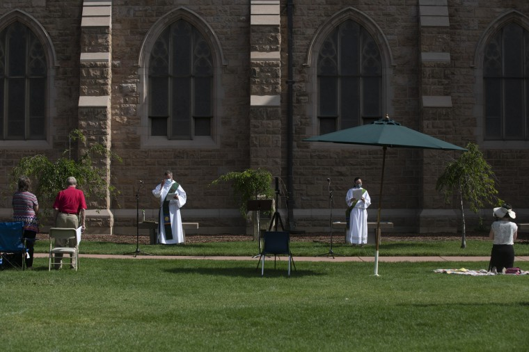 Gary Darress, a deacon, center left, and Claire Elser, a curate, lead worship services on July 19, 2020, at Grace and St. Stephen's Episcopal Church in Colorado Springs, Colorado. The church offers outdoor, socially distant Sunday worship services.