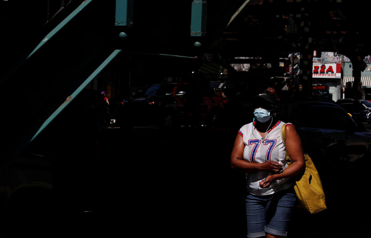 Image: A woman wearing a protective face mask walks in the Brighton Beach section of the Brooklyn,