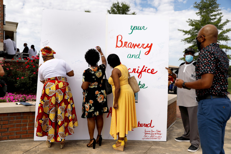 Image: People sign an oversize card for the family of the late U.S. Congressman John Lewis, a pioneer of the civil rights movement and long-time member of the U.S. House of Representatives who died July 17, at Troy University's Trojan Arena in Troy