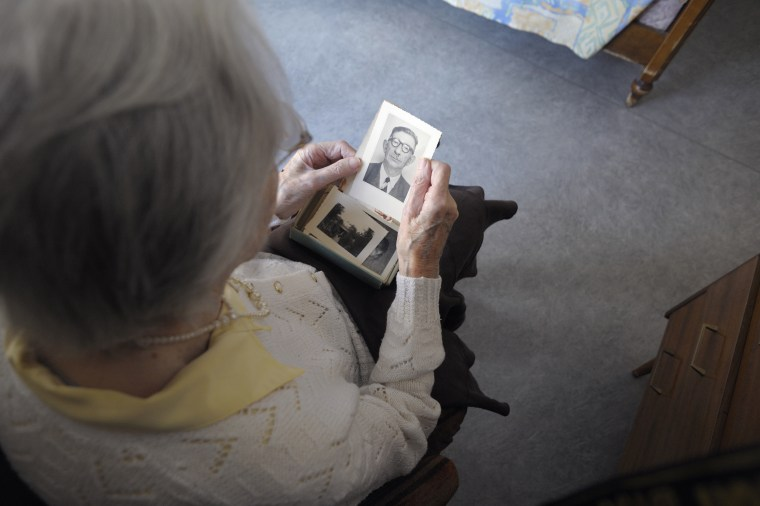 A woman suffering from Alzheimer's disease looks at an old picture in a retirement house in Angervilliers, eastern France, on March 18, 2011.