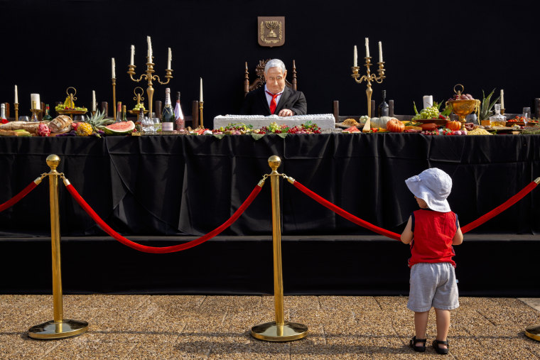 """Image: A child looks at an installation depicting Prime Minister Benjamin Netanyahu at a mock \""""Last Supper\"""""""