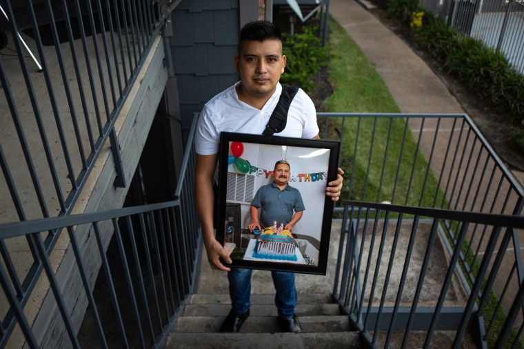 Cristobal Onofre holds up a framed photo of his father, who died from COVID-19 earlier this month, outside his home in Houston.