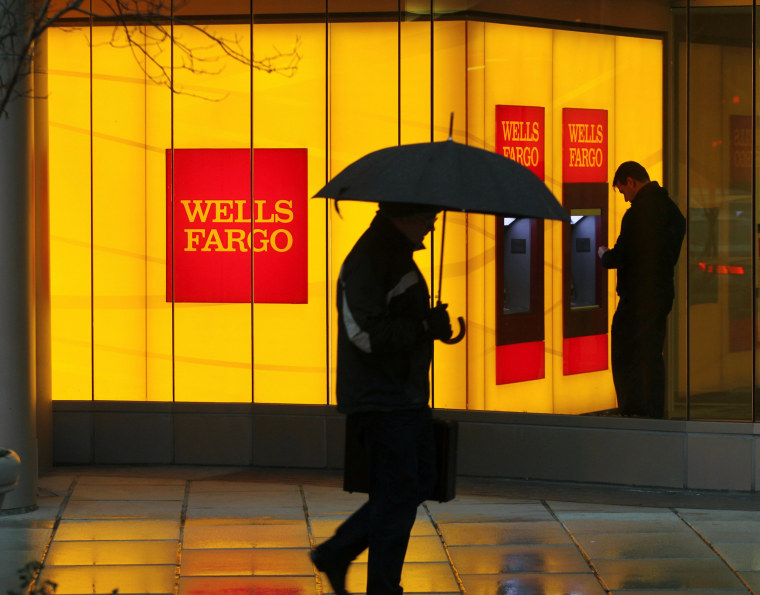 Image: A man walks past a Wells Fargo Bank branch on a rainy morning in Washington
