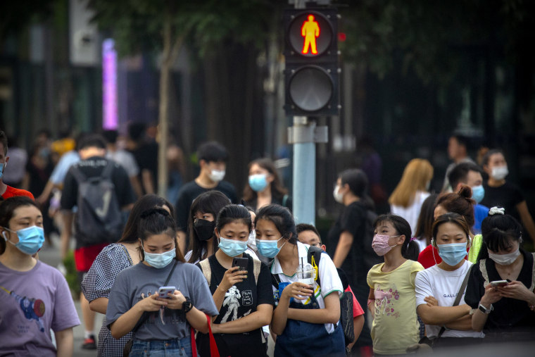 Image: People wearing face masks to protect against the coronavirus wait to cross an intersection in Beijing