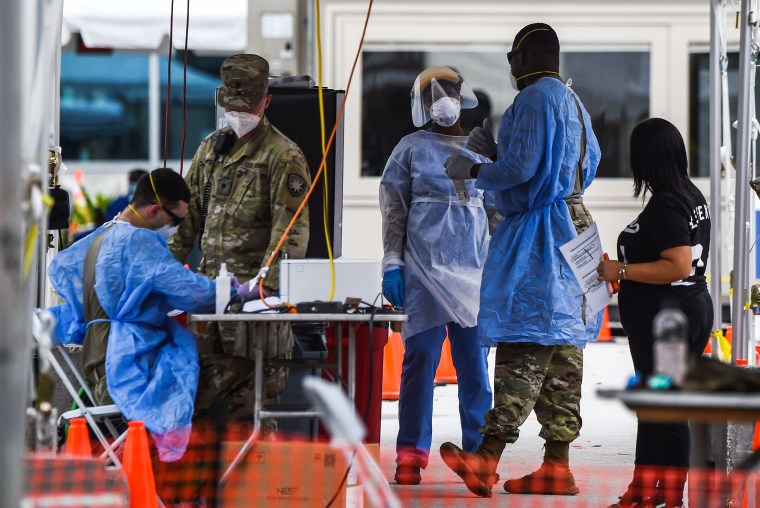 """Image: Medical personnel conduct coronavirus tests at a """"walk-in"""" and """"drive-through"""" site in Miami Beach"""