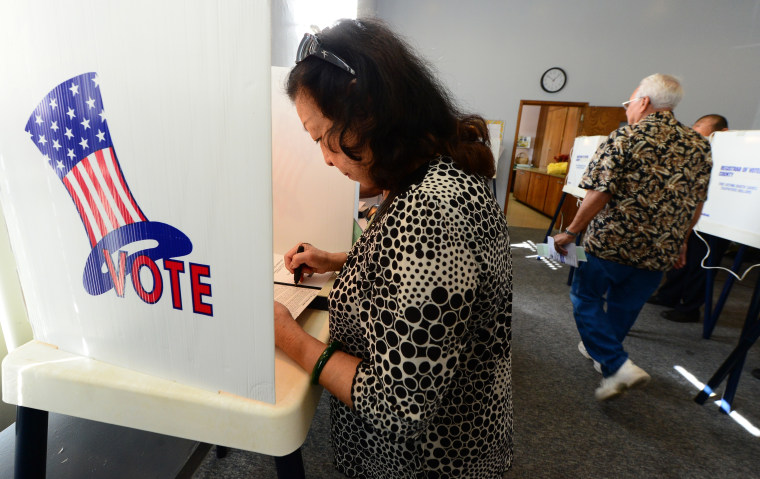 A woman votes at a polling station at St. Paul's Lutheran Church in Monterey Park, Los Angeles County