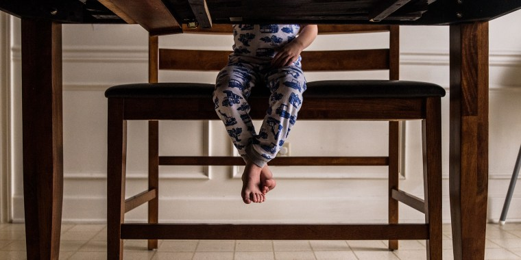 feet of young boy dangling off tall bench seen from underneath table