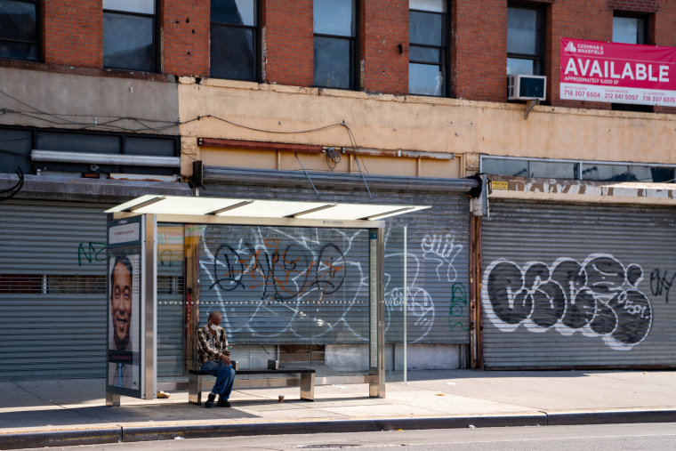 A person sits at a bus stop next to closed businesses in the Brooklyn borough of New York City on June 17, 2020.