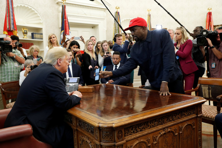 Rapper Kanye West shows President Trump his mobile phone during meeting in the Oval Office at the White House in Washington