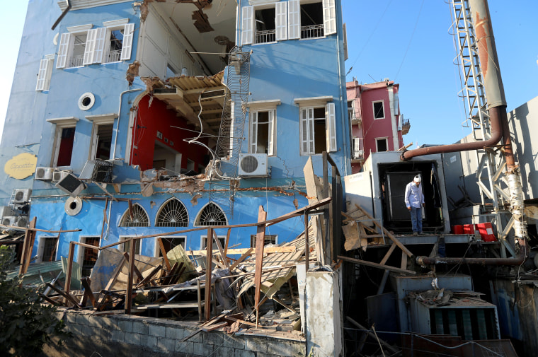 Image: A man inspects the damage following Tuesday's blast in Beirut's port area