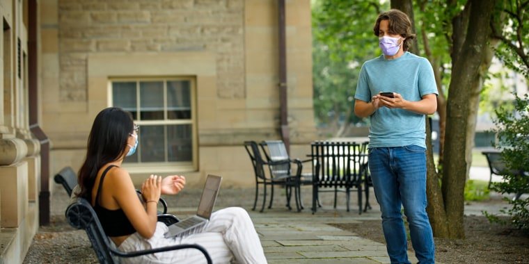 Bryan Maley, right, a Cornell University grad student in the Master of Public Health program, interviews a student on campus about mask-wearing experiences as part of a public health survey at the school on July 30.