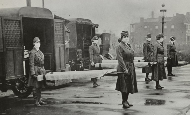 Red Cross Motor Corps. members holding stretchers behind ambulances in St. Louis