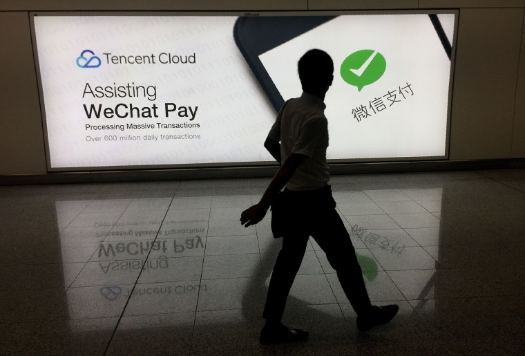 A man walks past an advertisement for the social media platform WeChat in Hong Kong's international airport on Aug. 21, 2017.
