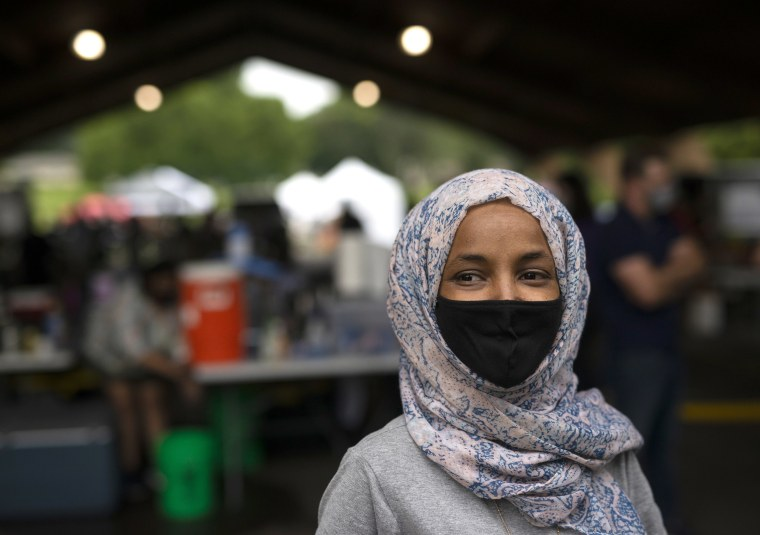Image: Rep. Ilhan Omar (D-MN) speaks with local television journalists while campaigning at the Richfield Farmers Market