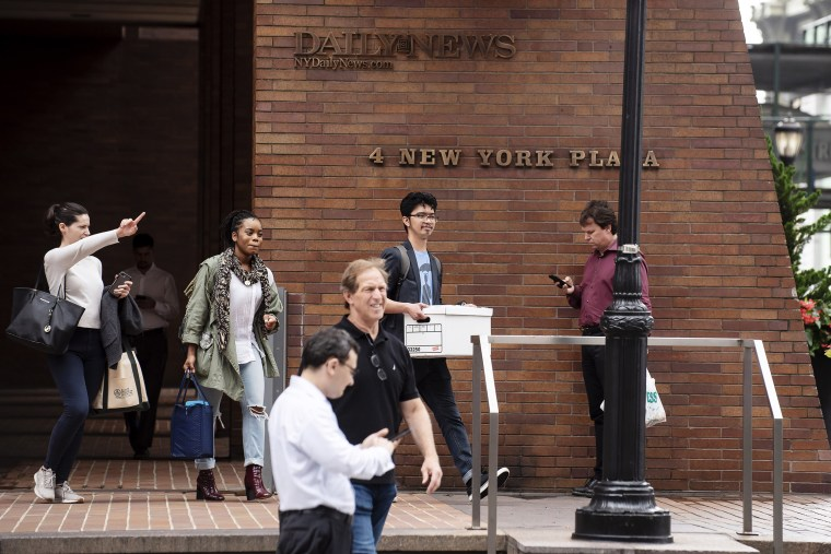 New York Daily News staff are seen carrying out their belongings at the company's headquarters in Manhattan.