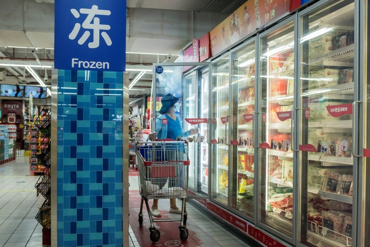 Image: A woman looks at frozen food products in a supermarket in Beijing