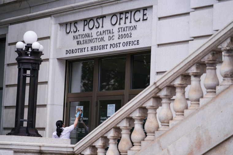 Image: A woman cleans the doors of the National Capital Station U.S. Post Office near Capitol Hill in Washington
